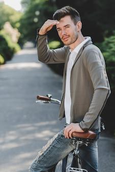 Junger gutaussehender mann auf dem fahrrad, das auge abschirmt