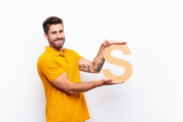 Junger gutaussehender mann aufgeregt, glücklich, freudig, den buchstaben s des alphabets haltend, um ein wort oder einen satz zu bilden.