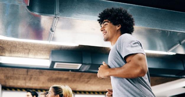 Junger gutaussehender mann beim cardio-training auf dem laufband im fitnessstudio