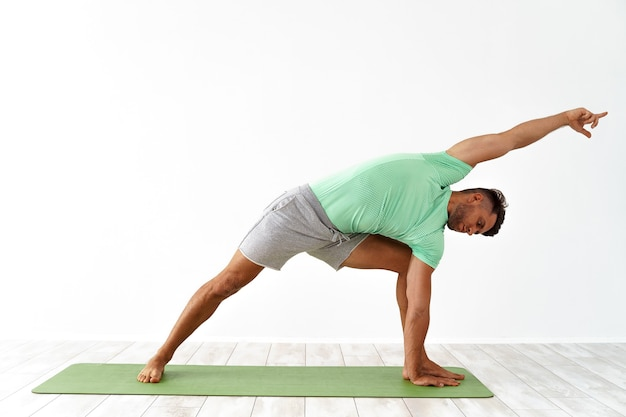 Junger gutaussehender mann beim yoga isoliert auf weiß