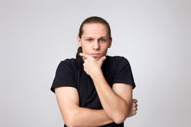 Junger gutaussehender mann berührt sein kinn mit der hand und denkt isoliert auf grauem hintergrund