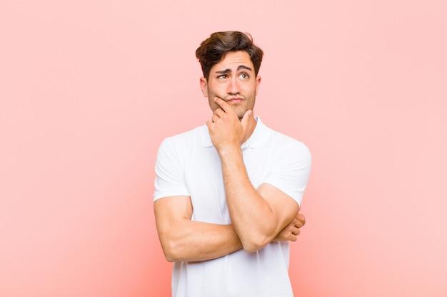 Junger gutaussehender mann denkt, fühlt sich zweifelhaft und verwirrt, mit verschiedenen optionen, fragt sich, welche entscheidung gegen rosa wand zu treffen ist