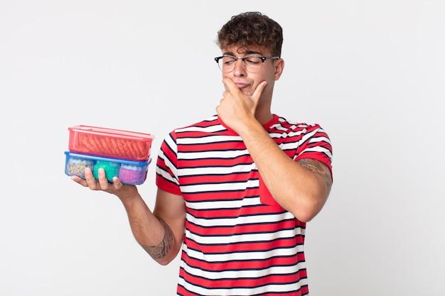 Junger gutaussehender mann denkt, fühlt sich zweifelnd und verwirrt und hält eine lunchbox