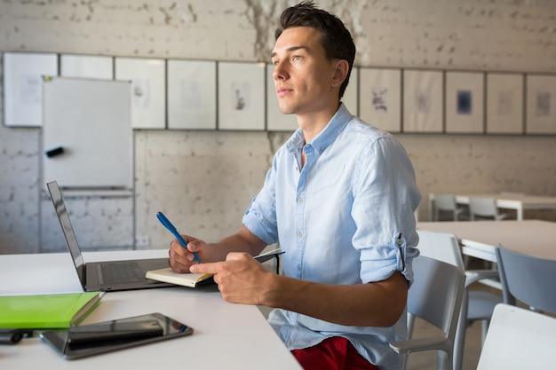 Junger gutaussehender mann denkt, notizen in notizbuch schreibend