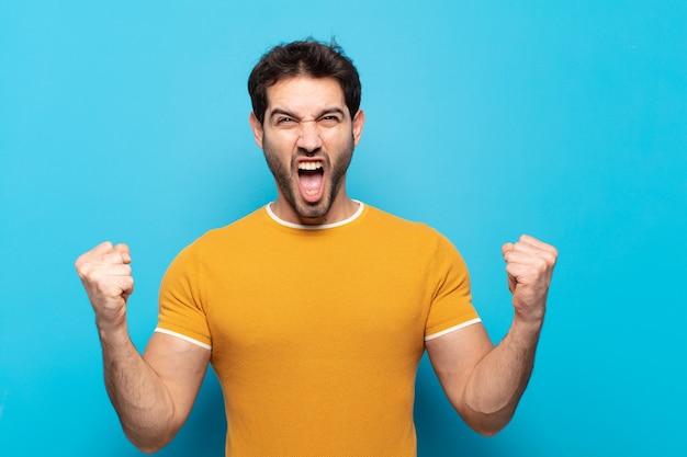 Junger gutaussehender mann, der aggressiv mit einem wütenden ausdruck oder mit geballten fäusten schreit, um den erfolg zu feiern