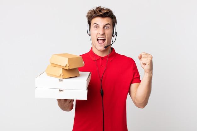 Junger gutaussehender mann, der aggressiv mit einem wütenden ausdruck schreit. take-away-fast-food-konzept