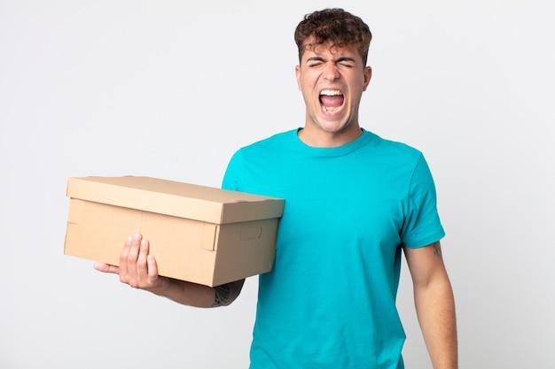 Junger gutaussehender mann, der aggressiv schreit, sehr wütend aussieht und einen karton hält
