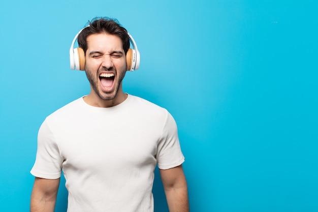 Junger gutaussehender mann, der aggressiv schreit, sehr wütend, frustriert, empört oder genervt aussieht und nein schreit