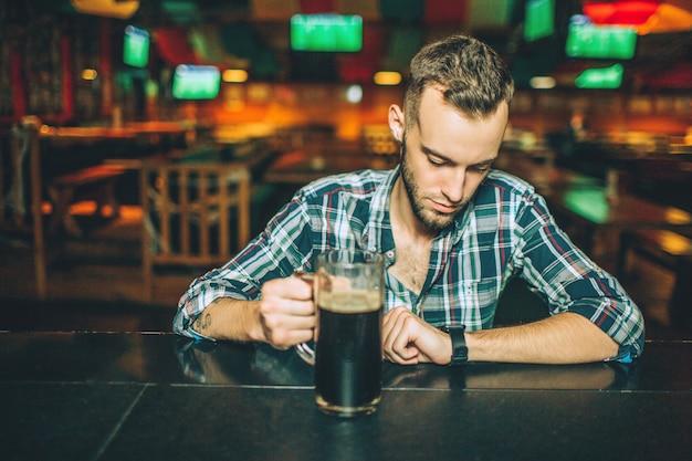 Junger gutaussehender mann, der allein am stangenzähler in der kneipe sitzt. er hält einen krug bier in der hand und schaut auf die uhren.