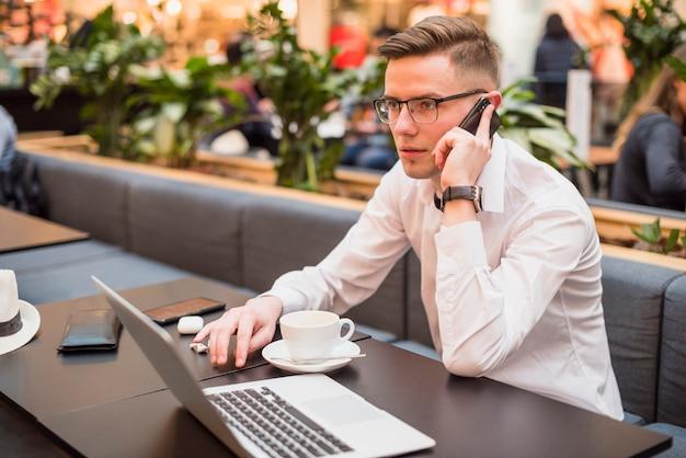 Junger gutaussehender mann, der am handy im café mit laptop auf tabelle spricht
