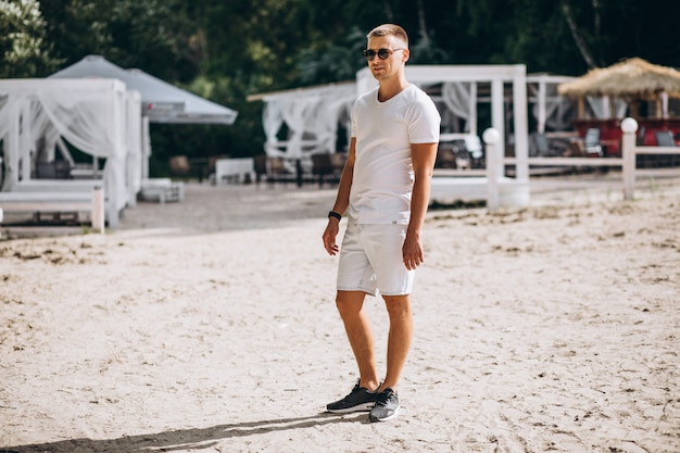 Junger gutaussehender mann, der am strand durch den park steht