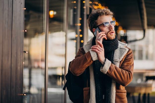 Junger gutaussehender mann, der am telefon durch den flughafen spricht
