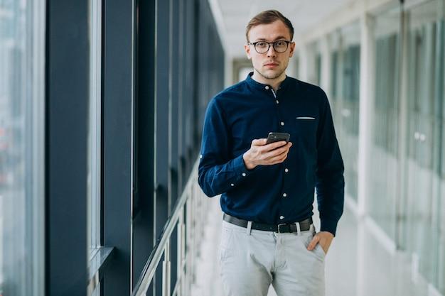 Junger gutaussehender mann, der am telefon im büro spricht