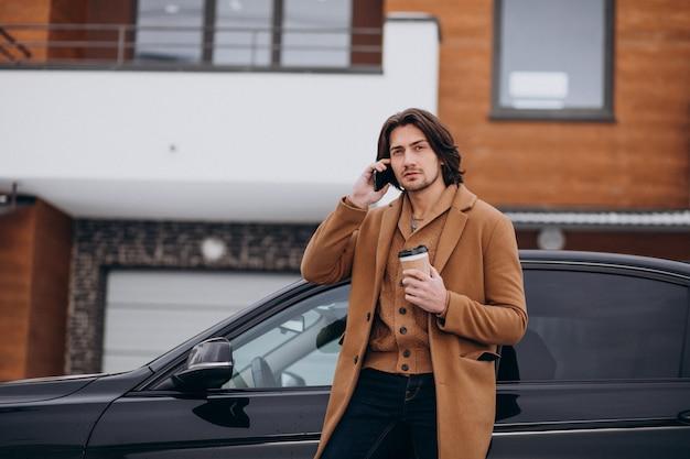 Junger gutaussehender mann, der am telefon mit seinem auto spricht