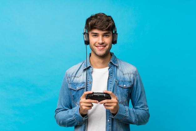 Junger gutaussehender mann, der an den videospielen spielt