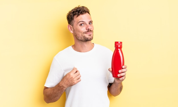 Junger gutaussehender mann, der arrogant, erfolgreich, positiv und stolz aussieht. ketchup-konzept