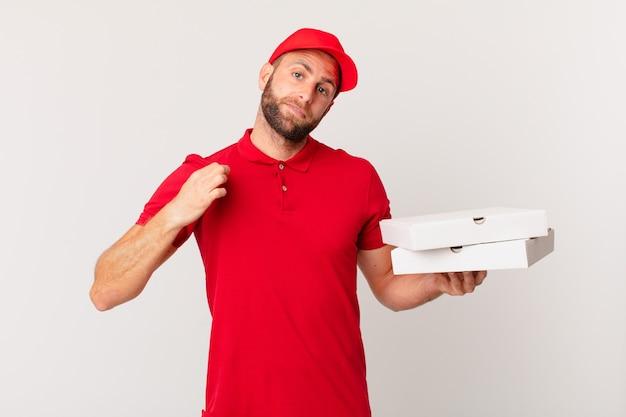 Junger gutaussehender mann, der arrogant, erfolgreich, positiv und stolz aussieht. pizza lieferkonzept