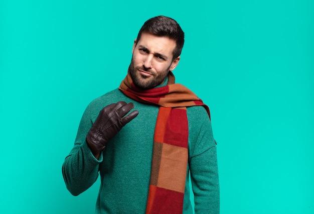Junger gutaussehender mann, der arrogant, erfolgreich, positiv und stolz aussieht und auf sich selbst zeigt. kalt und winter concetp