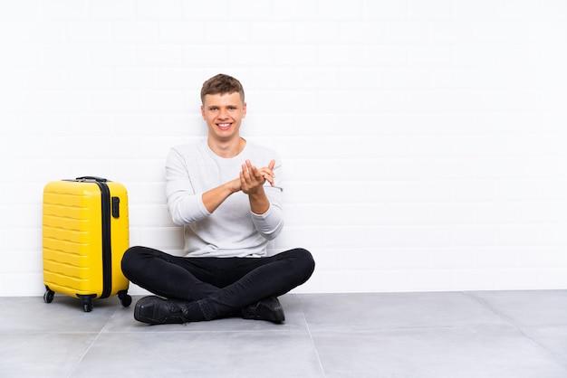 Junger gutaussehender mann, der auf dem boden mit einem applaudierenden koffer sitzt