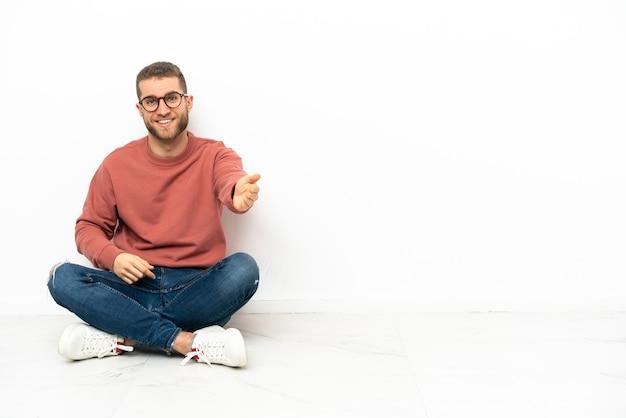 Junger gutaussehender mann, der auf dem boden sitzt und sich die hände schüttelt, um ein gutes geschäft abzuschließen?