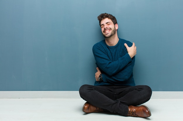 Junger gutaussehender mann, der auf dem boden sitzt und sich verliebt fühlt, lächelt, kuschelt und sich umarmt, ledig bleibt, egoistisch und egozentrisch ist