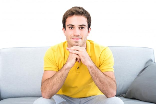 Junger gutaussehender mann, der auf der couch im wohnzimmer sitzt