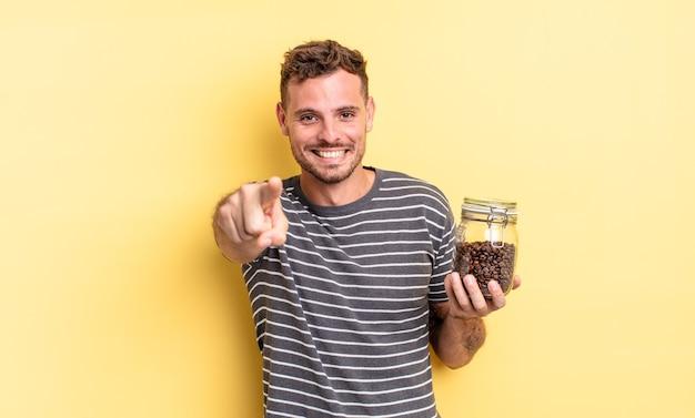 Junger gutaussehender mann, der auf die kamera zeigt, die ihr kaffeebohnenkonzept wählt