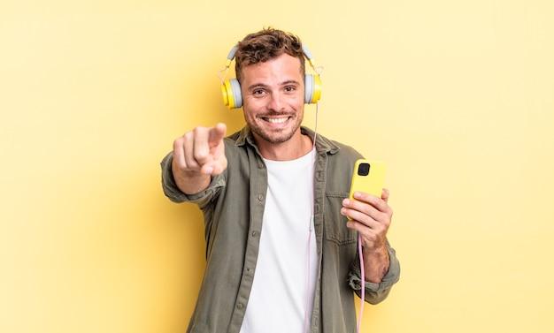 Junger gutaussehender mann, der auf die kamera zeigt, die ihr kopfhörer- und smartphone-konzept auswählt