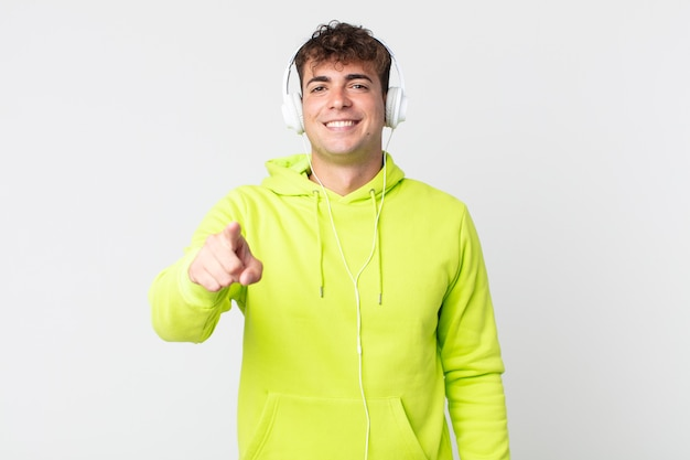 Junger gutaussehender mann, der auf die kamera zeigt, die sie und kopfhörer auswählt