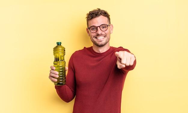 Junger gutaussehender mann, der auf die kamera zeigt, die sie wählt. olivenöl konzept