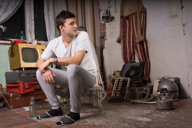 Junger gutaussehender mann, der auf käfig im junk room sitzt und den rechten rahmen betrachtet.