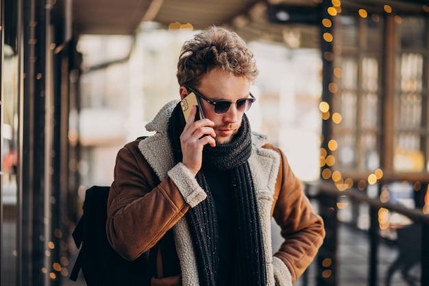 Junger gutaussehender mann, der auf smartphone spricht