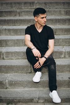 Junger gutaussehender mann, der auf treppe sitzt