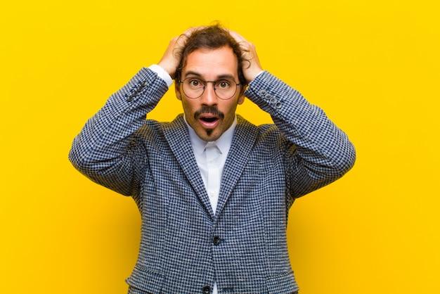 Junger gutaussehender mann, der aufgeregt und überrascht, mit beiden händen auf kopf mit offenem mund schaut und wie ein glücklicher sieger gegen orange sich fühlt