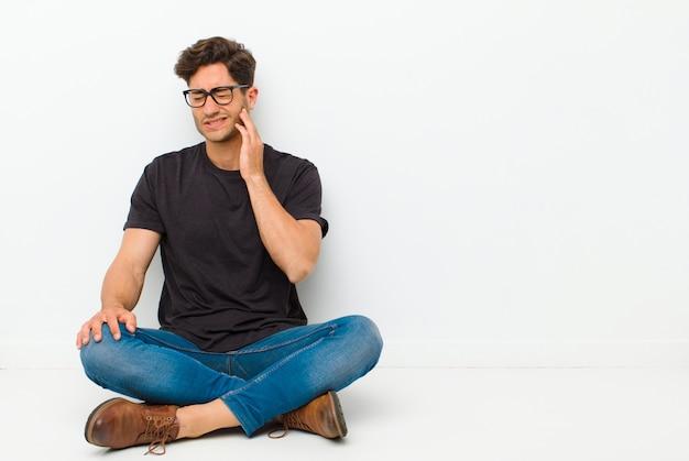 Junger gutaussehender mann, der backe hält und schmerzliche zahnschmerzen erleidet