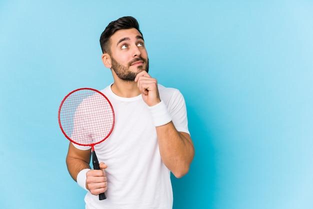 Junger gutaussehender mann, der badminton spielt, isoliert seitwärts schauend mit zweifelhaftem und skeptischem ausdruck.