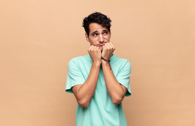 Junger gutaussehender mann, der besorgt, ängstlich, gestresst und ängstlich aussieht, fingernägel beißt und zum seitlichen kopierraum schaut