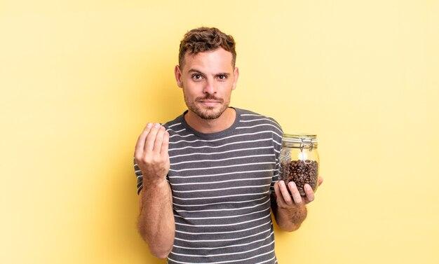 Junger gutaussehender mann, der capice oder geldgeste macht und ihnen sagt, dass sie das kaffeebohnenkonzept bezahlen sollen