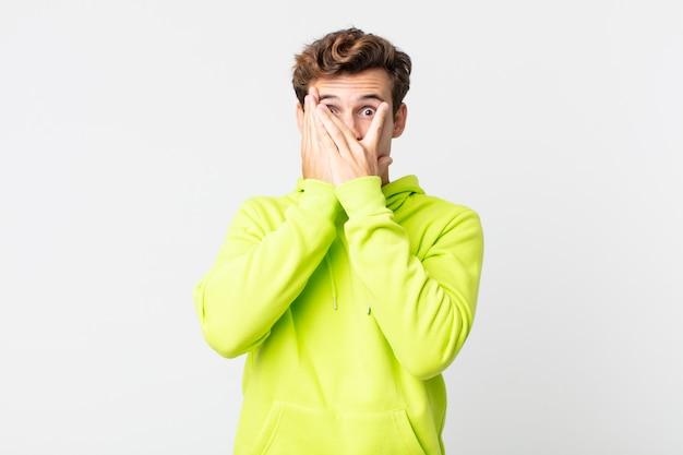 Junger gutaussehender mann, der das gesicht mit den händen bedeckt, mit überraschtem ausdruck zwischen den fingern späht und zur seite schaut