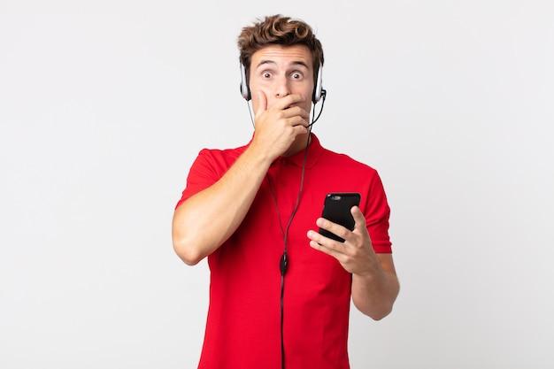 Junger gutaussehender mann, der den mund mit den händen bedeckt, mit einem schock mit einem smartphone und einem headset