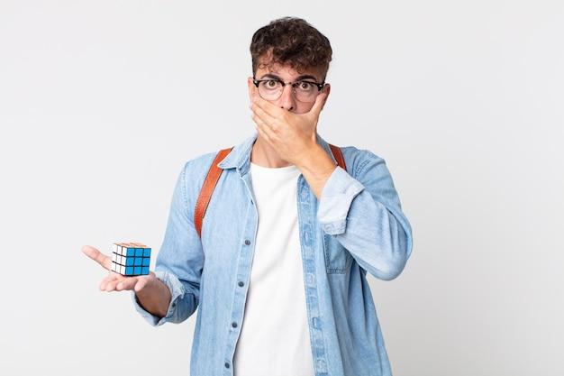 Junger gutaussehender mann, der den mund mit den händen mit einem schockierten bedeckt. intelligenzspielkonzept