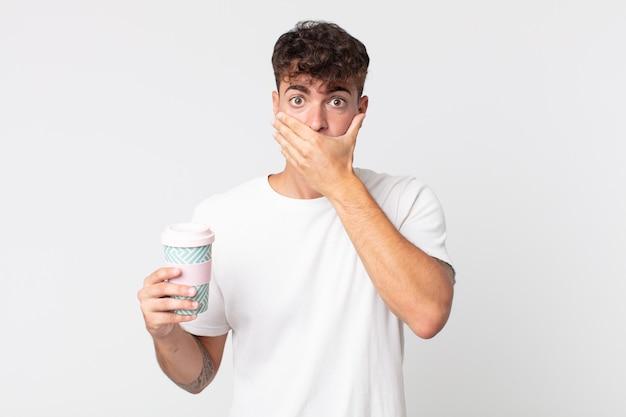 Junger gutaussehender mann, der den mund mit den händen mit einem schockierten bedeckt und einen kaffee zum mitnehmen hält