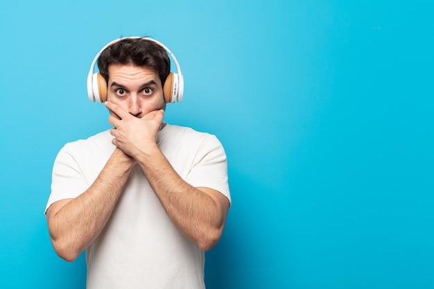 Junger gutaussehender mann, der den mund mit den händen mit einem schockierten, überraschten ausdruck bedeckt, ein geheimnis hält oder oops sagt