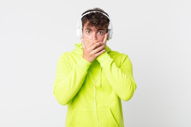 Junger gutaussehender mann, der den mund mit den händen mit einem schockierten und kopfhörer bedeckt