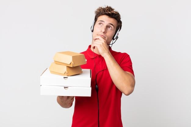 Junger gutaussehender mann, der denkt, sich zweifelhaft und verwirrt fühlt. take-away-fast-food-konzept