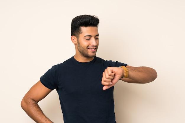 Junger gutaussehender mann, der die armbanduhr schaut