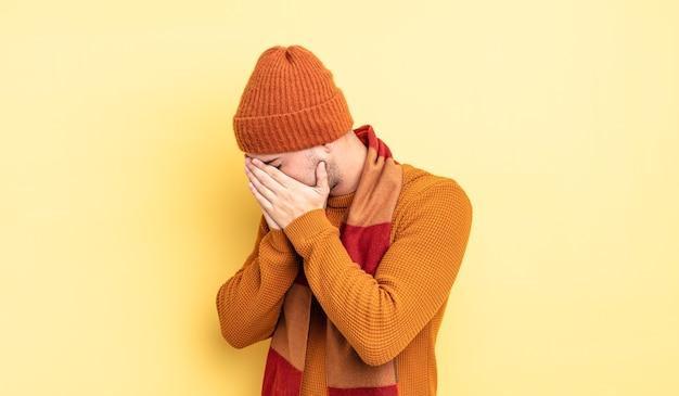 Junger gutaussehender mann, der die augen mit den händen bedeckt, mit einem traurigen, frustrierten blick der verzweiflung, weinen, seitenansicht