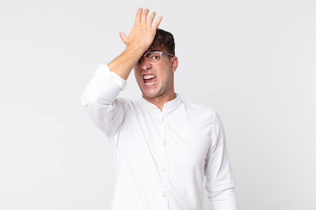 Junger gutaussehender mann, der die handfläche zur stirn hebt und denkt, oops, nachdem er einen dummen fehler gemacht oder sich daran erinnert hat, sich dumm zu fühlen