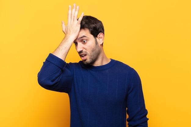 Junger gutaussehender mann, der die handfläche zur stirn hebt und denkt, oops, nachdem er einen dummen fehler gemacht oder sich erinnert hat, sich dumm fühlt