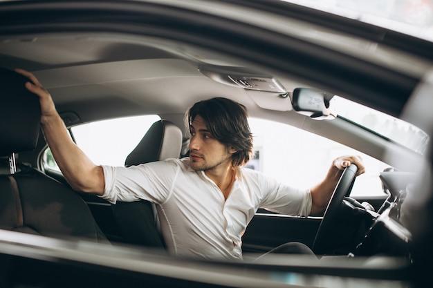 Junger gutaussehender mann, der ein auto in einem autosalon wählt